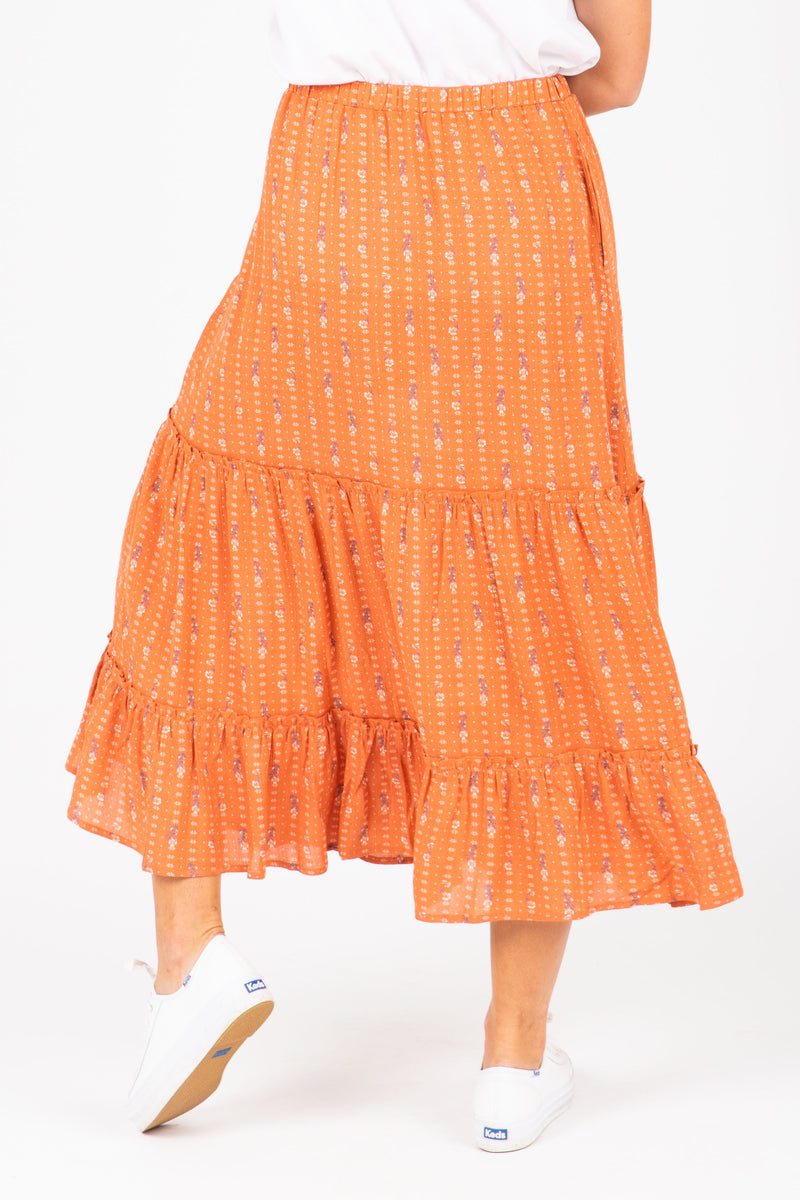 The Danna Floral Tiered Skirt in Rust, studio shoot; back view