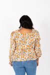 The Karyn Smocked Peplum Blouse in Mustard, studio shoot; back view