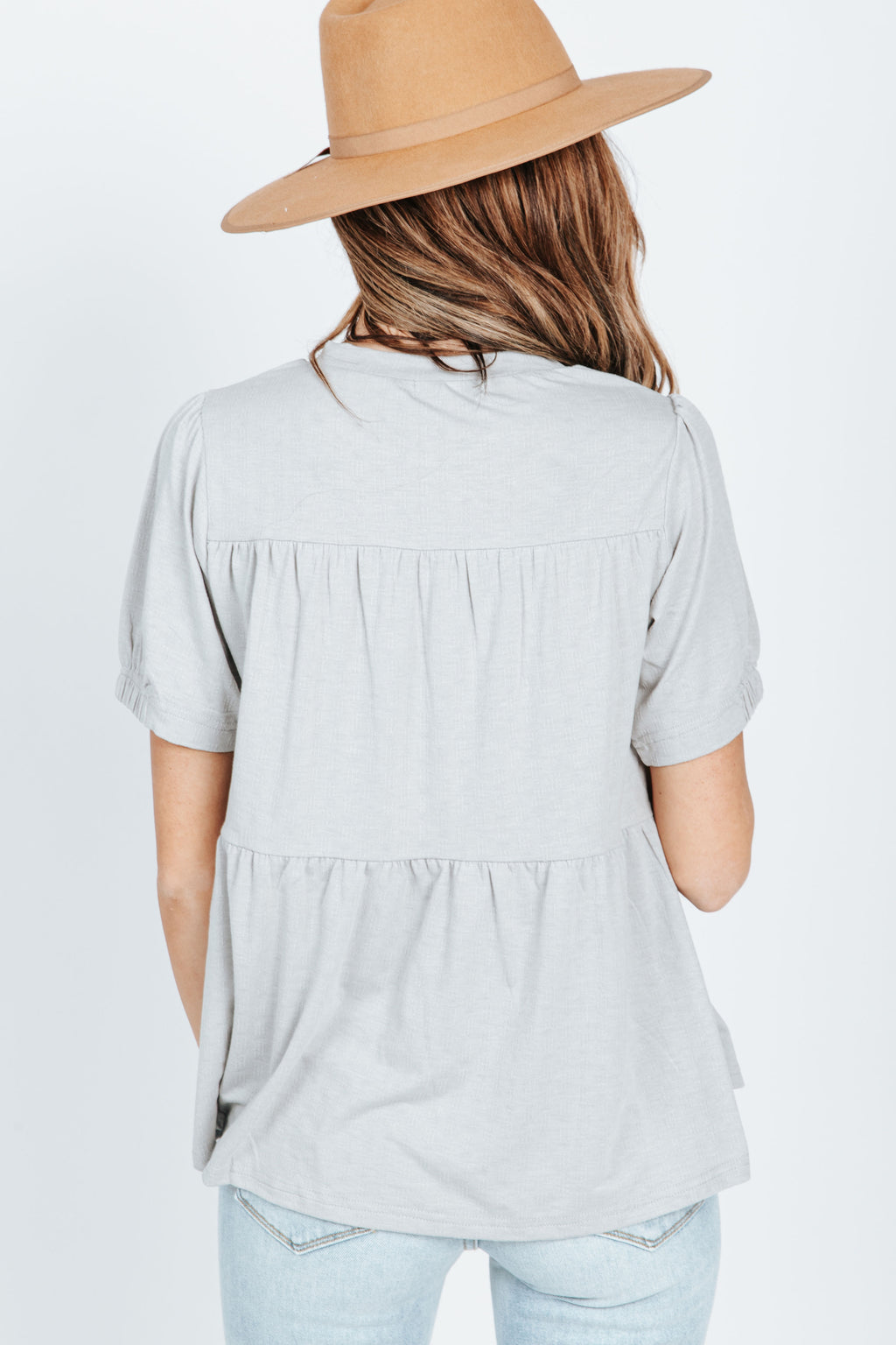The Jon Tiered Peplum in Heather Grey, studio shoot; back view