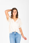 The Ari Button Ruffle Blouse in Cream, studio shoot; front view