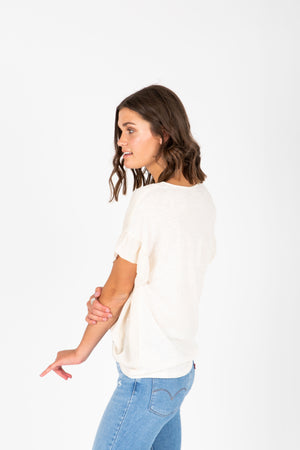 The Ari Button Ruffle Blouse in Cream, studio shoot; side view