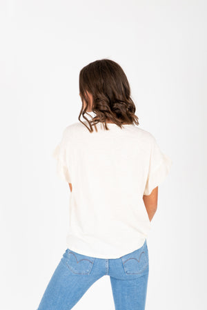 The Ari Button Ruffle Blouse in Cream, studio shoot; back view