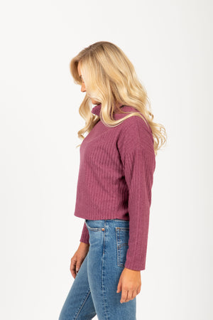 The Boreal Ribbed Turtleneck Blouse in Mauve, studio shoot; side view