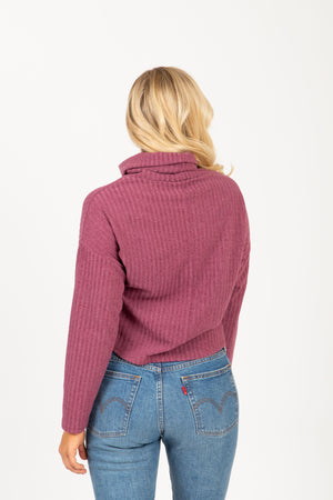 The Boreal Ribbed Turtleneck Blouse in Mauve, studio shoot; back view