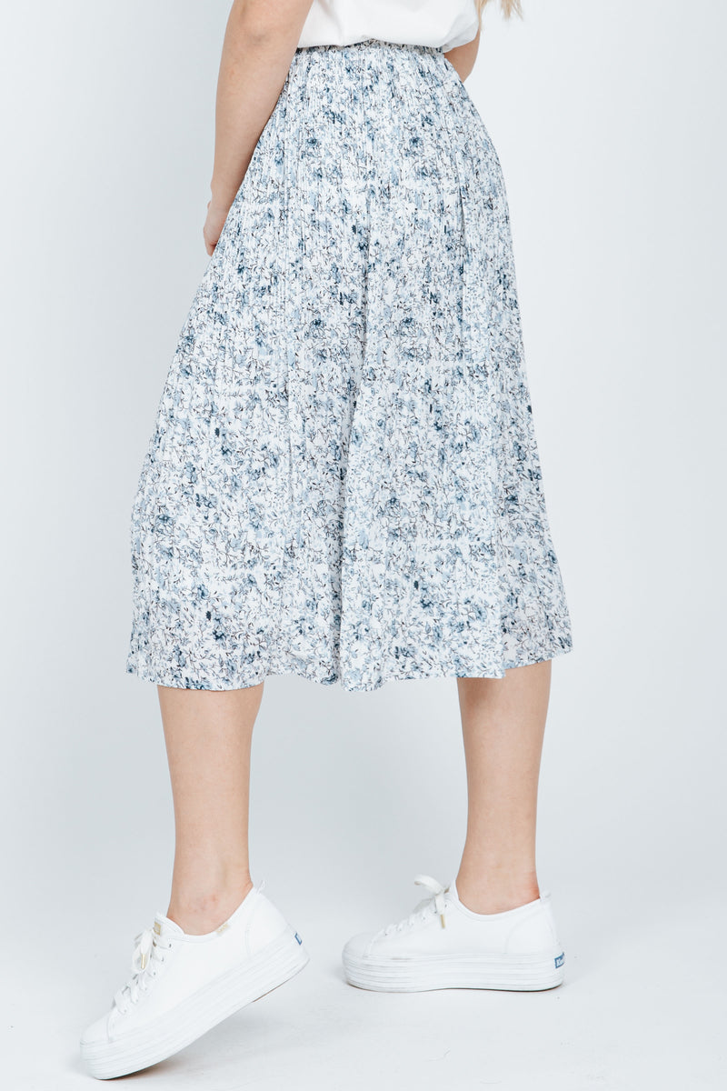 The Madelyn Pleated Skirt in Blue, studio shoot; side view