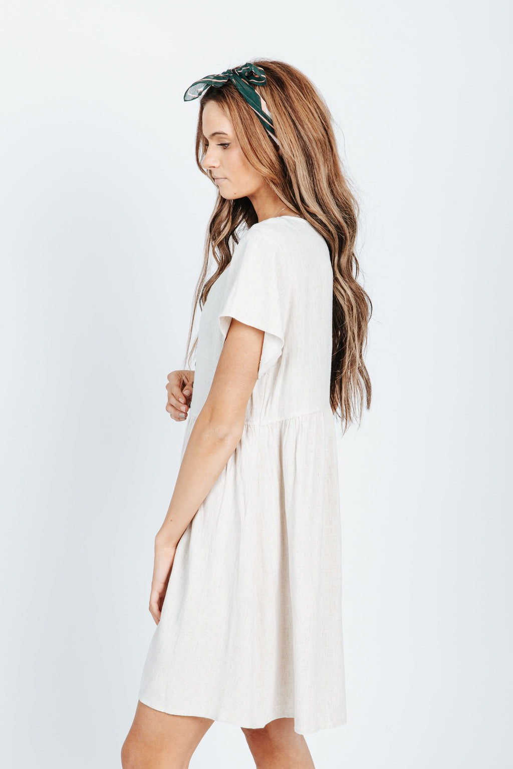 The Jenny Linen Button Front Dress in Natural, studio shoot; side view