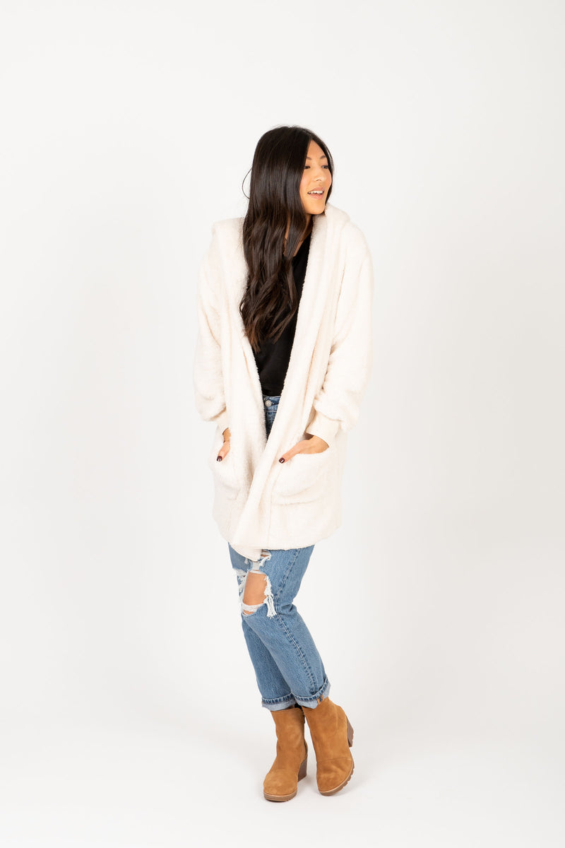 The Reach Cozy Hooded Cardigan in Ivory, studio shoot; front view with hands in side pockets