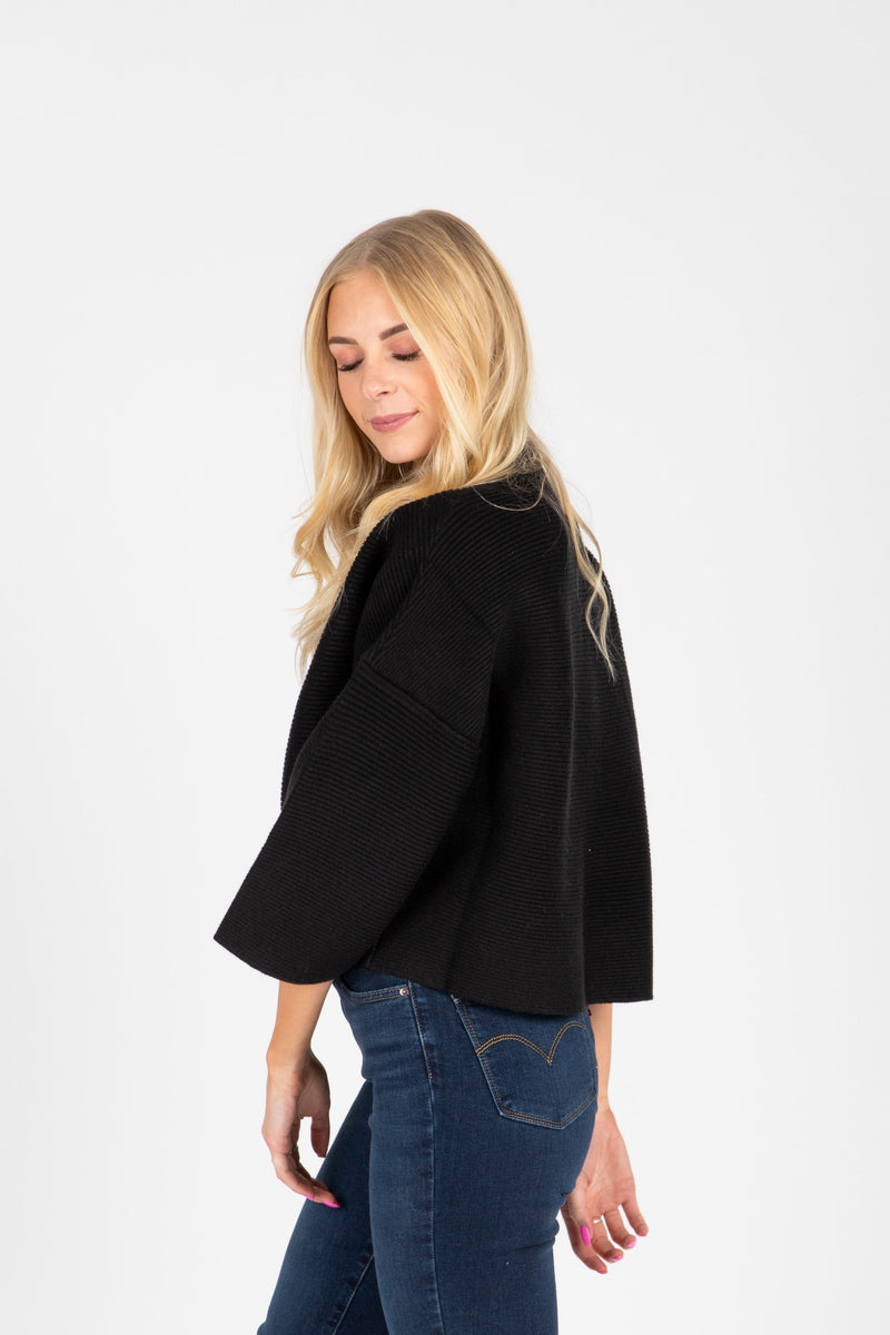 The William Ribbed Mock Neck Sweater in Black, studio shoot; side view