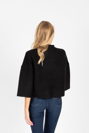 The William Ribbed Mock Neck Sweater in Black, studio shoot; back view