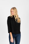 The William Ribbed Mock Neck Sweater in Black, studio shoot; front view