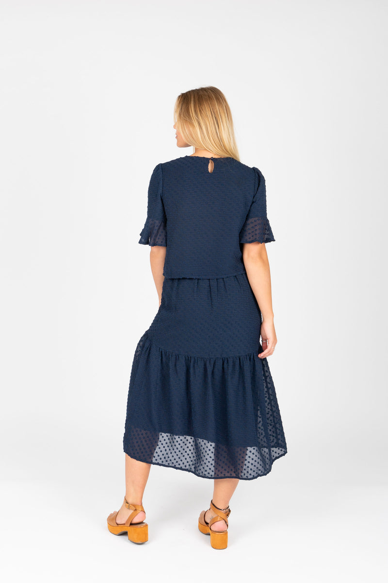 The Skipper Swiss Dot Blouse in Navy, studio shoot; back view