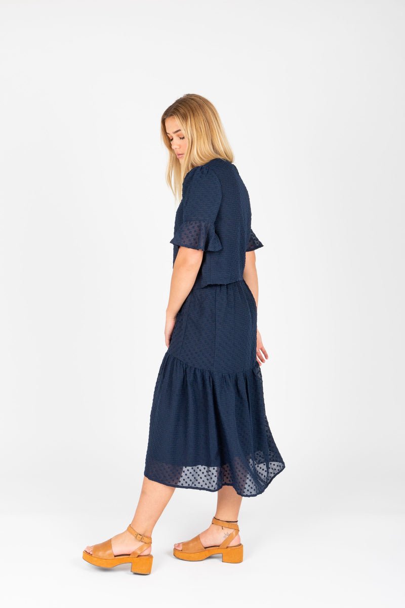 The Skipper Swiss Dot Skirt in Navy, studio shoot; side view