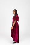 The Banton Pleated Velvet Maxi Dress in Burgundy, lifestyle shoot; side view