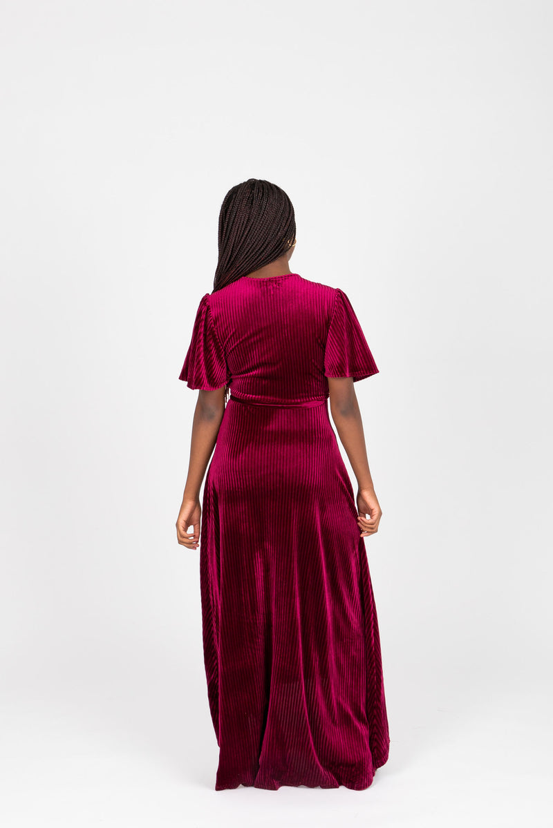 The Banton Pleated Velvet Maxi Dress in Burgundy, lifestyle shoot; back view
