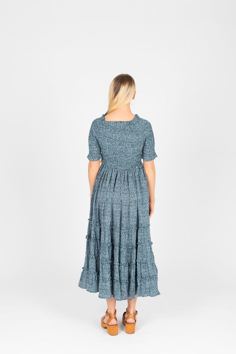 The Mumulo Pattern Smocked Tiered Dress in Blue, studio shoot; back view