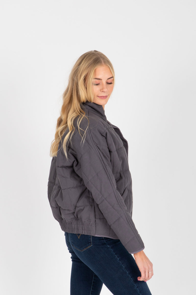 The Mindy Quilted Bomber Jacket in Charcoal, studio shoot; side view
