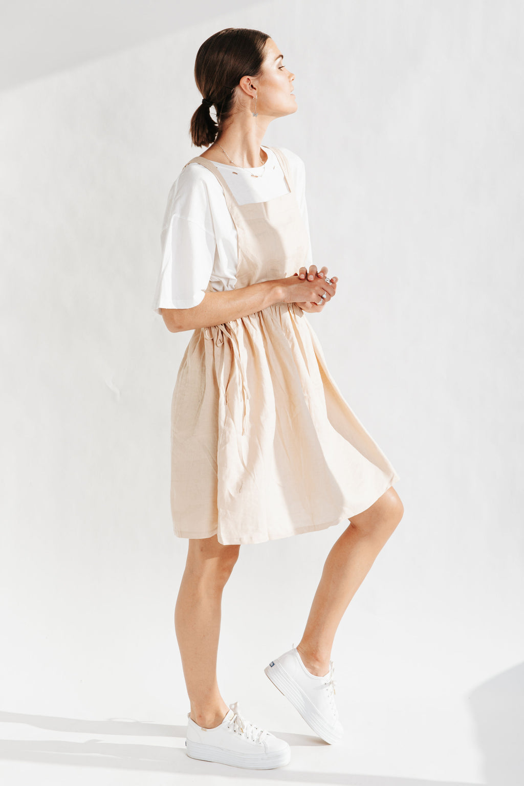 The Baltimore Linen Jumper Dress in Taupe, studio shoot; side view