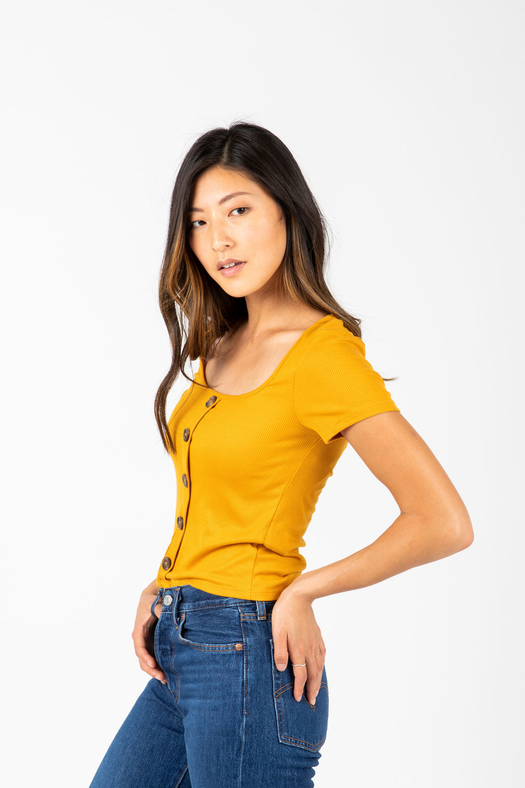 The Colfer Ribbed Button Blouse in Mustard, studio shoot; side view