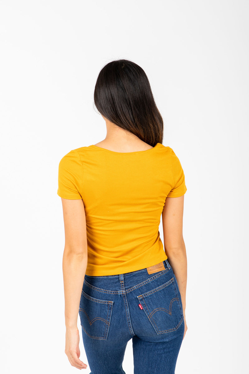 The Colfer Ribbed Button Blouse in Mustard, studio shoot; back view