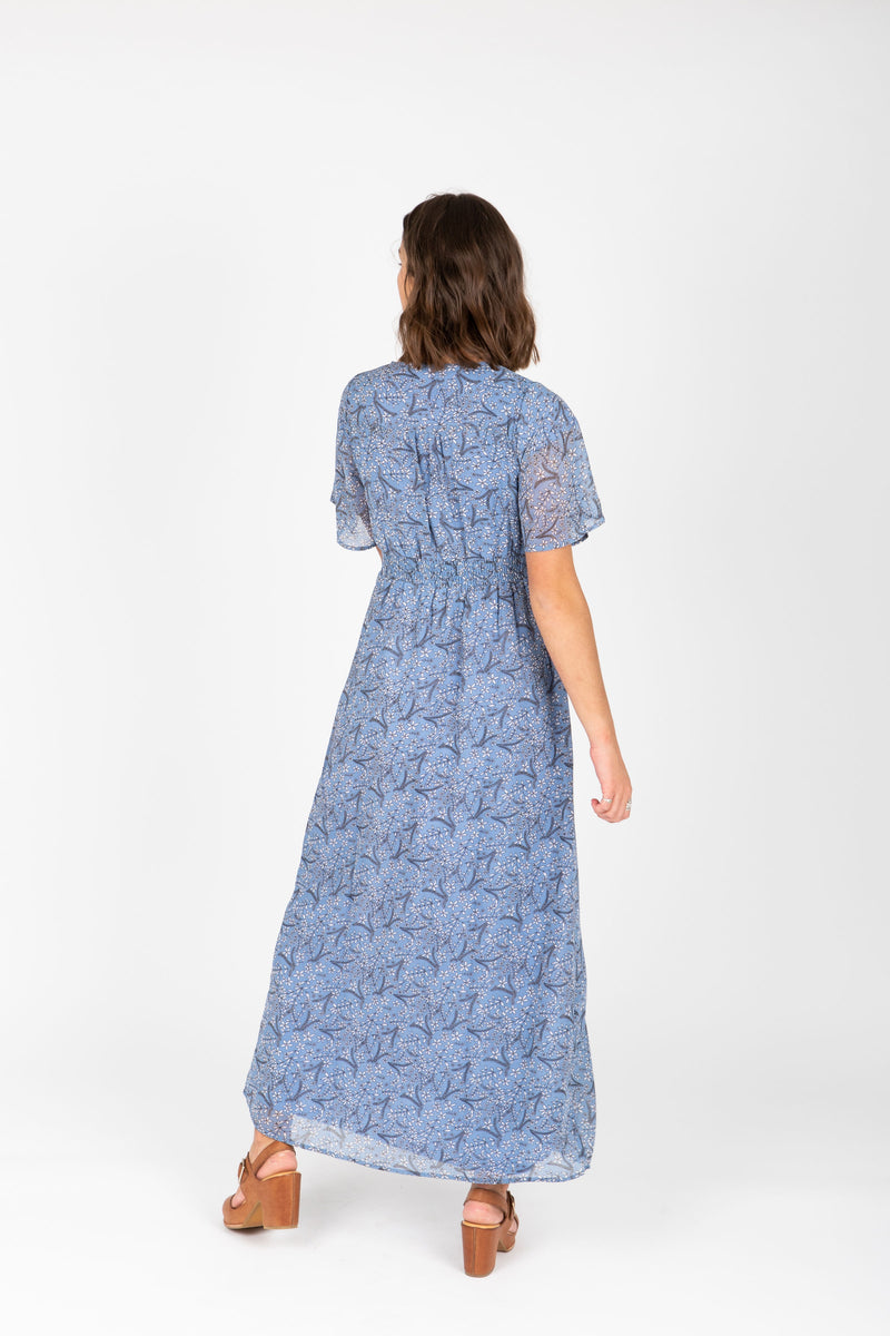 The Liana Floral Smocked Dress in Blue, studio shoot; back view