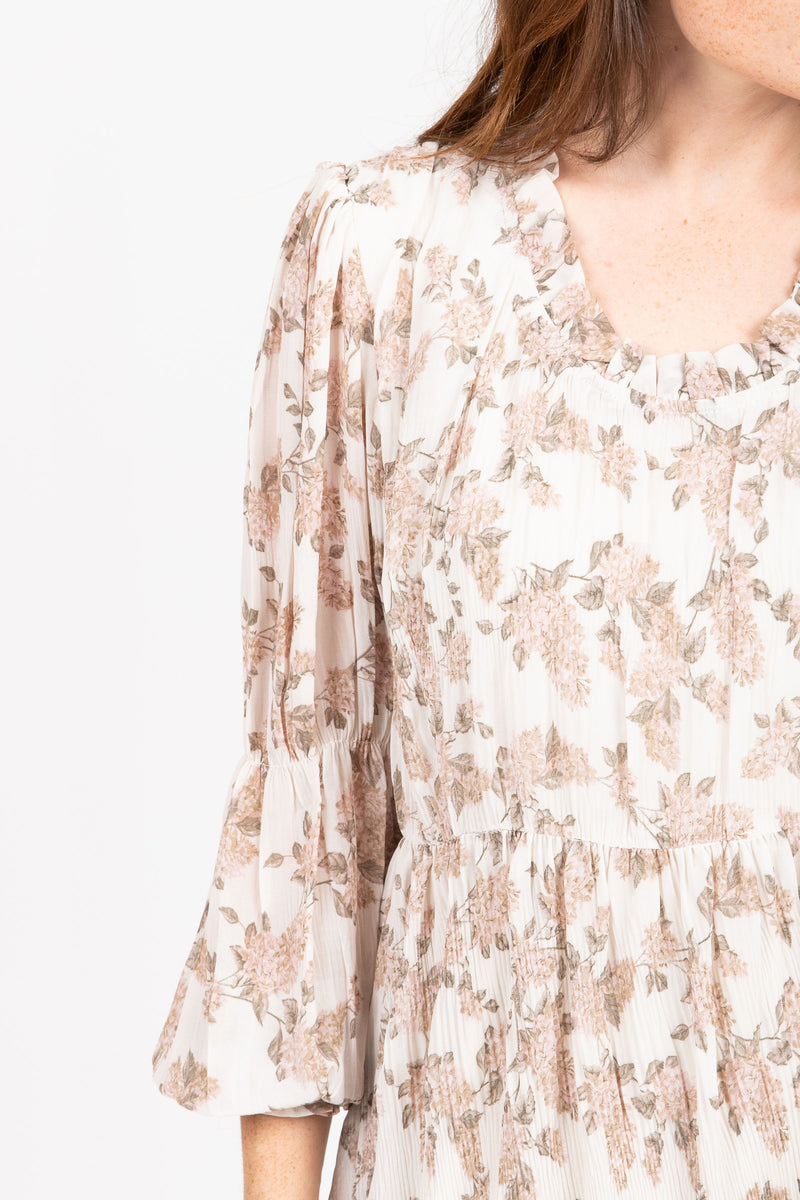 The Silvan Floral Pleated Dress in Ivory, studio shoot; closer up front view