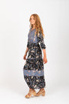 The Haskell Floral Contrast Maxi Dress in Black, studio shoot; side view