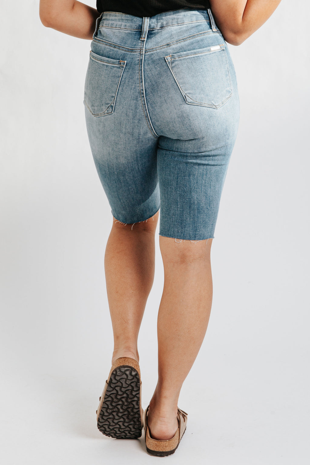 The Ashburn High Rise Denim Biker Short in Dark Wash, studio shoot; back view