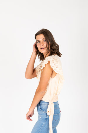 The Remy Lace Tie Blouse in Cream, studio shot; side view