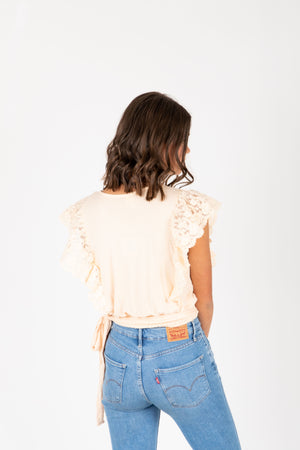 The Remy Lace Tie Blouse in Cream, studio shot; back view