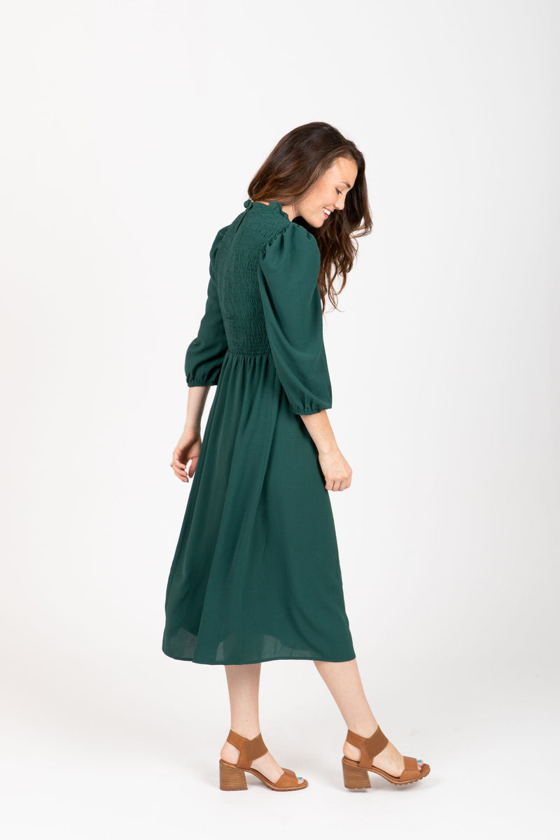 The Ezra Smocked Midi Dress in Hunter Green, studio shoot; side view
