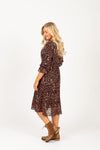 The Balderine Patterned Pleated Dress in Black, studio shoot; side view