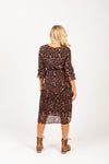 The Balderine Patterned Pleated Dress in Black, studio shoot; back view