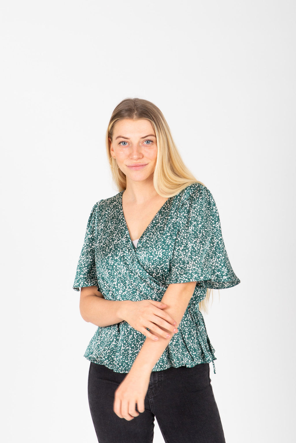 The Jolie Dot Wrap Blouse in Jewel Green, studio shoot; front view