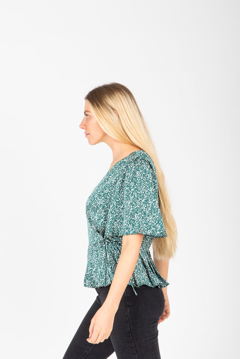 The Jolie Dot Wrap Blouse in Jewel Green, studio shoot; side view