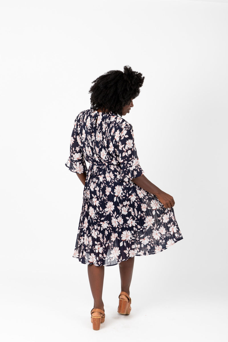 The Penny Floral Pleated Dress in Navy, studio shoot; back view