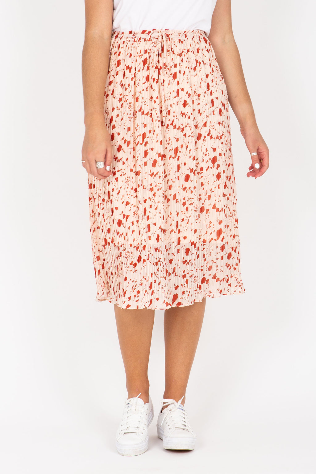 The Charli Patterned Pleated Skirt in Blush, studio shoot; front view