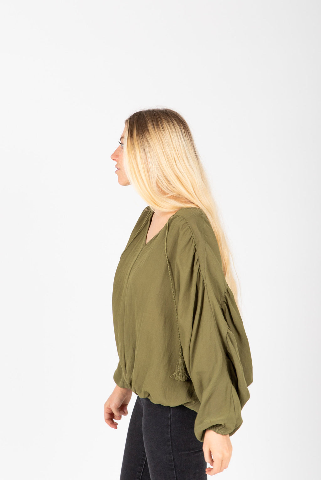 The Rink Tassel Detail Blouse in Olive, studio shoot; side view