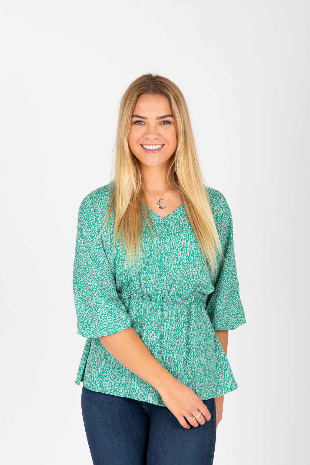 The Meadow Patterned Peplum Blouse in Green, studio shoot; front view