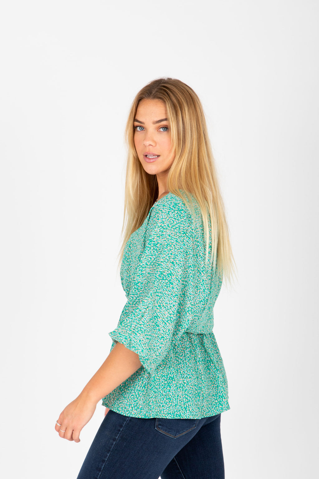 The Meadow Patterned Peplum Blouse in Green, studio shoot; side view