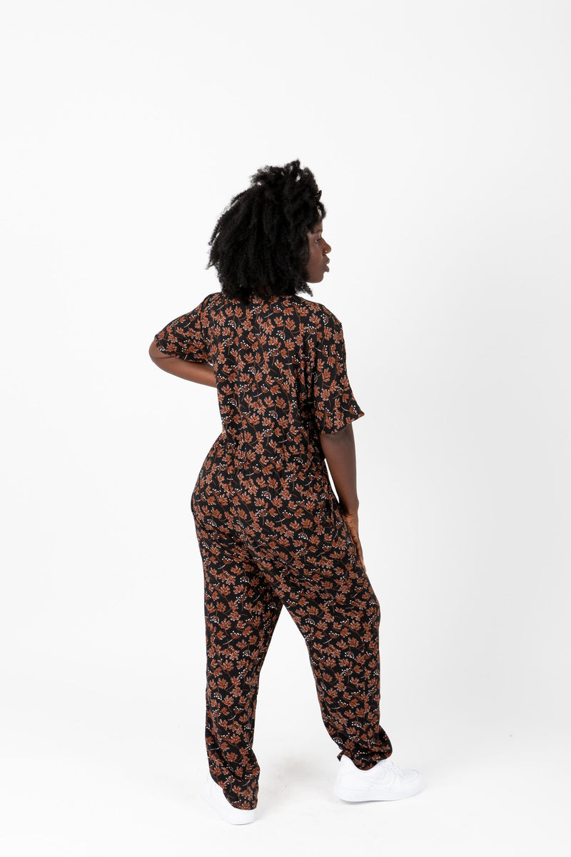 The Elliott Floral Wrap Jumpsuit in Black, lifestyle shoot; back view