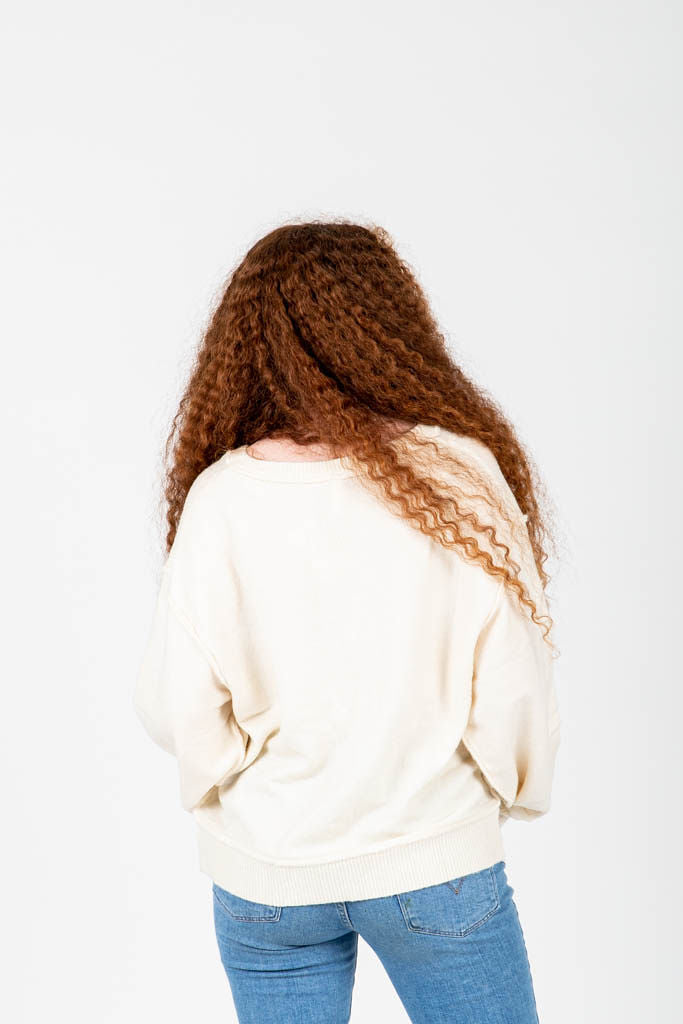 The Wynn Cozy V-Neck Pullover in Cream, studio shoot; back view