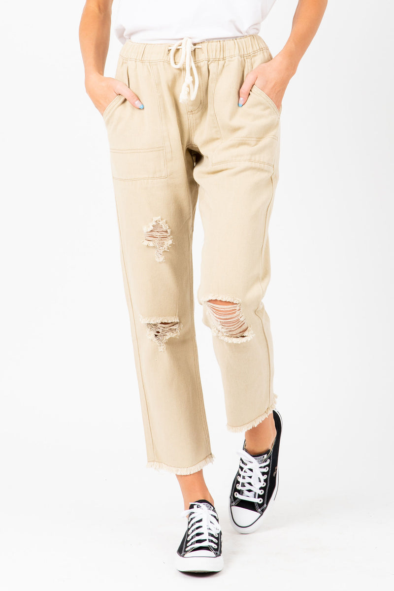 The Levy Distressed Trousers in Tan, studio shoot; front view
