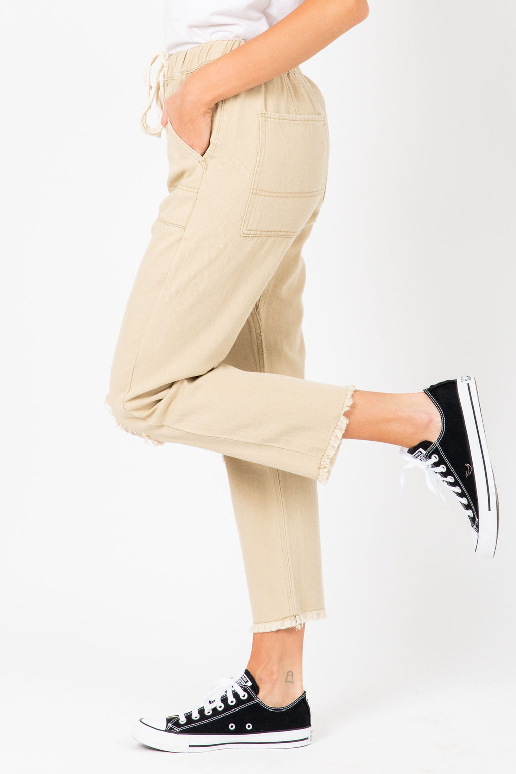 The Levy Distressed Trousers in Tan, studio shoot; side view