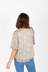 The Ava Floral Smocked Blouse in White, studio shoot; back view