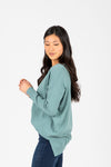 The Brant V-Neck Sweater in Teal, studio shoot; side view