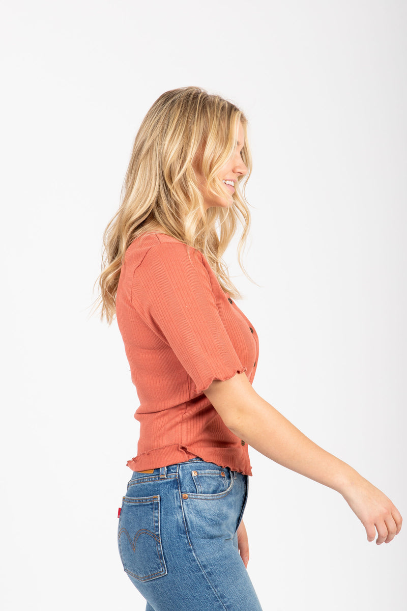 The Noa Ribbed Henley in Rust, studio shoot; side view