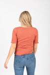 The Noa Ribbed Henley in Rust, studio shoot; back view