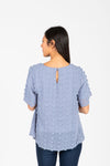 The Minta Swiss Dot Blouse in Sky, studio shoot; back view