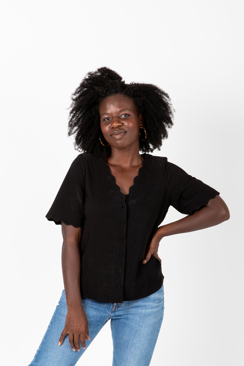 The Naya Scalloped Button Blouse in Black, studio shoot; front view