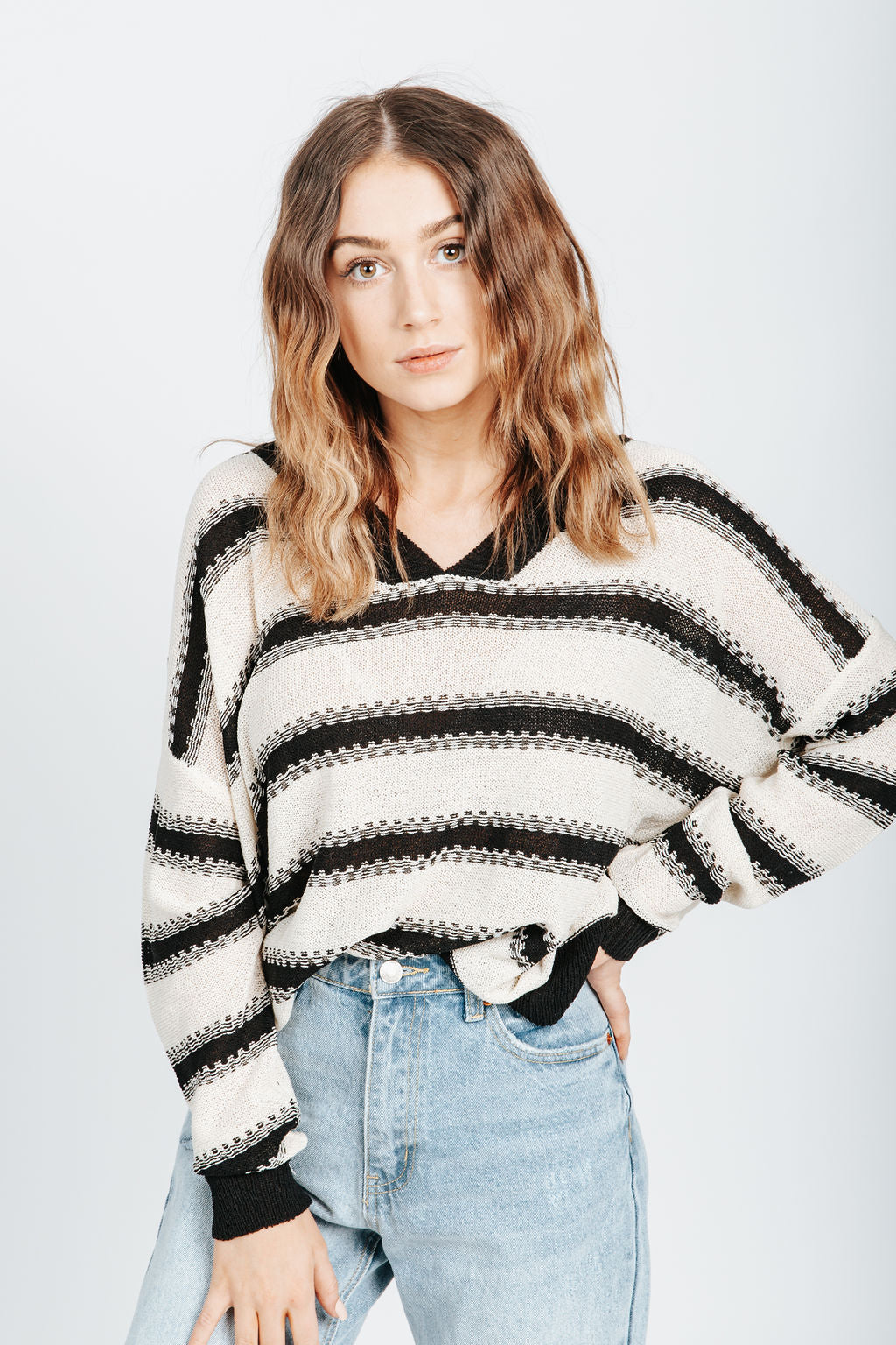 The Clarin Striped Sweater in Black, studio shoot; front view